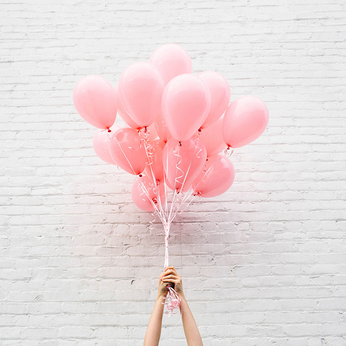 Two hands holding a bouquet of balloons